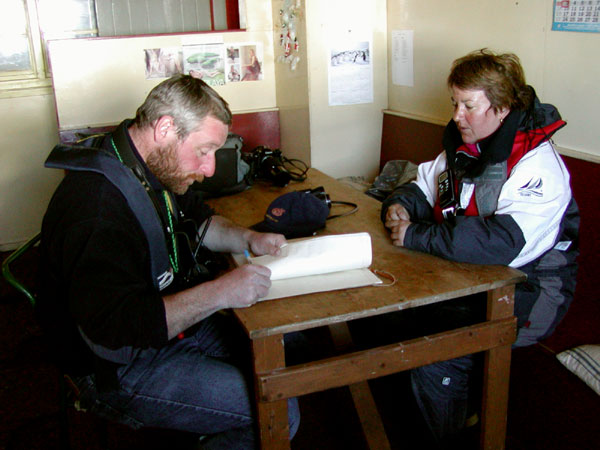 Martin (naturalist) and Monika (expedition leader) signing Danco Island guest book