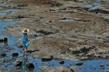 Girl with a sun hat at low tide