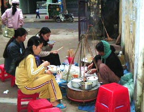 Students are taking the Breakfast on street side restaurant in hue