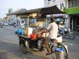 a street vendor pedals his cart to work