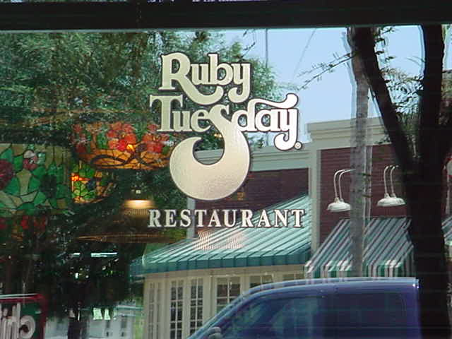 a sign in a reflection <br>Ruby Tuesday restaurant