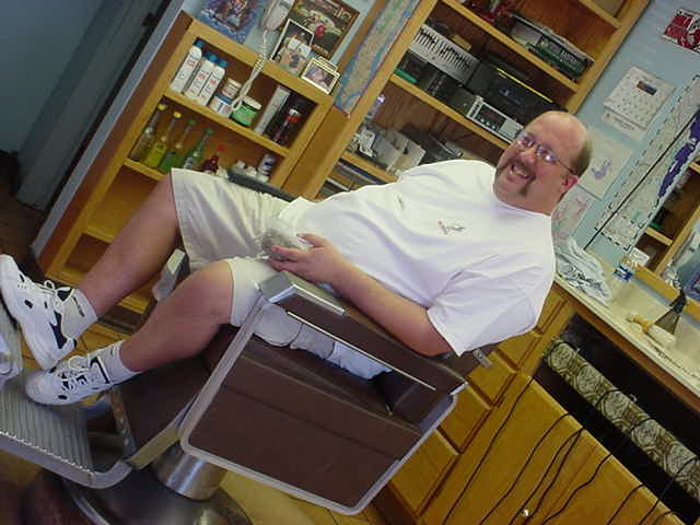 bill leaning back in his barber Bill chair