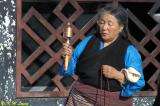 An old lady was rotating a prayer wheel