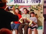 The boys have their picture made with the snake.