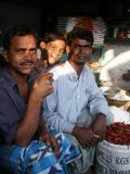Boy lit up with 2 men at produce market, Dhaka