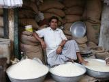 Rice seller relaxing with his wares, Dhaka