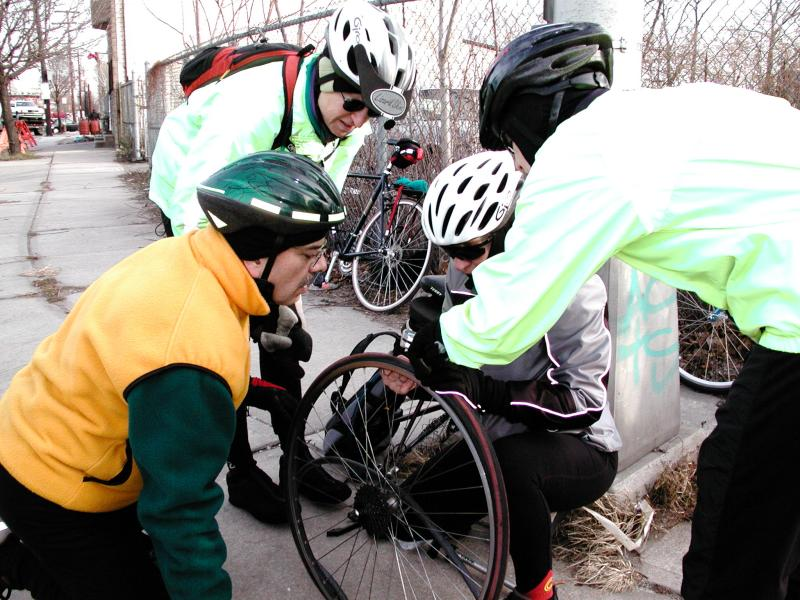 Photo from Rong.Trudy finds a piece of glass in her tire with Linda, Rong, and Jane looking on.