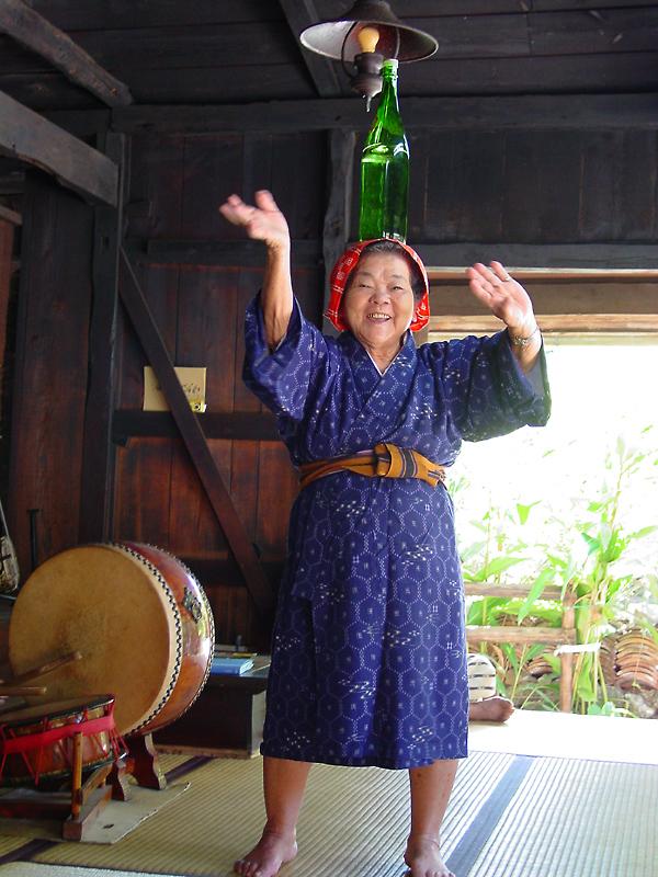 Lady dancing with awamori on her head
