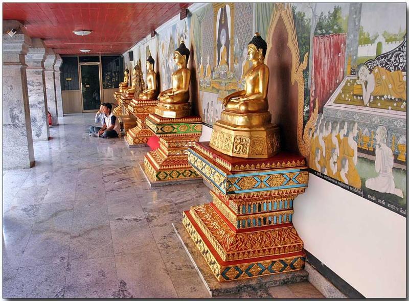 Buddha idols facing the golden chedi