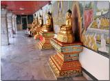Buddha idols facing the golden chedi
