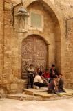 Local kids hanging out in front of an ornate door in medieval Sidon