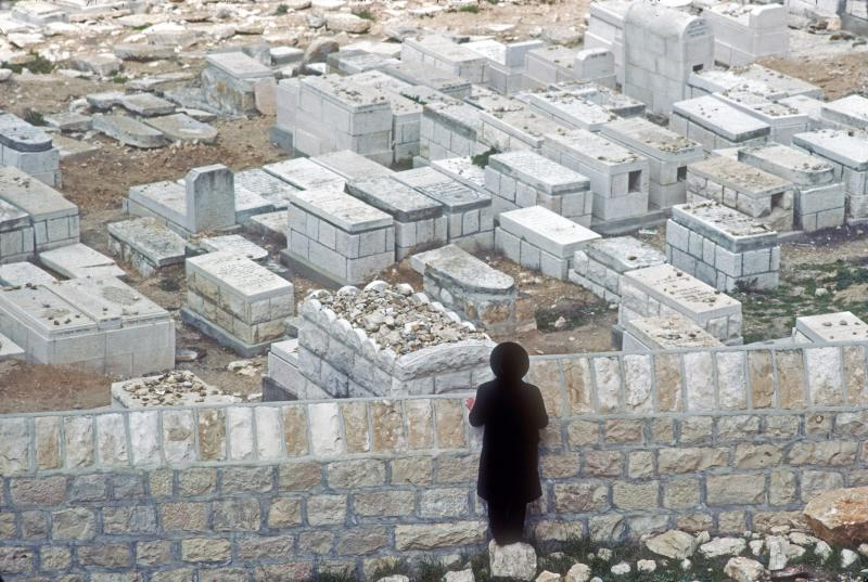 Rabbi Throwing Stones at Graves of Loved Ones -- As He is Not Permitted to Enter a Cemetery