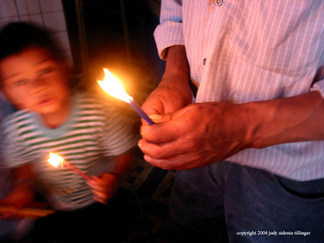 father and son with candles, san andreas iztapa, guatemala