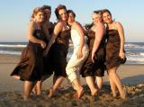 Sabrina, Ronda, and the bridesmaids pose on the beach.
