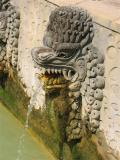 carved stone naga spew water from the natural hot spring into the bath