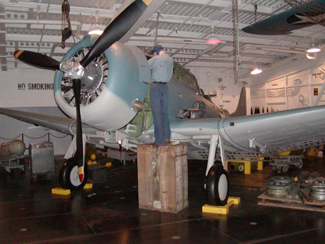 Mechanic working on a Douglas Dauntless dive bomber in the hangar bay