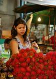 Woman at a fruit stand with rambutans, Bangkok