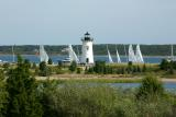 The Edgartown Lighthouse surrounded by sailboats in the harbor.