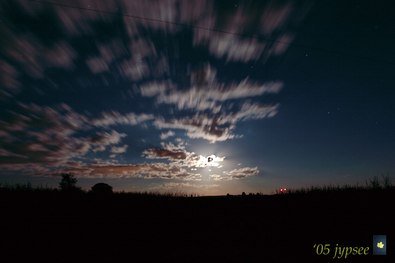 green corn moon emerging from moving clouds