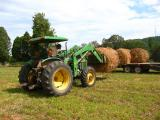 John Deere tractor putting hay on a trailer