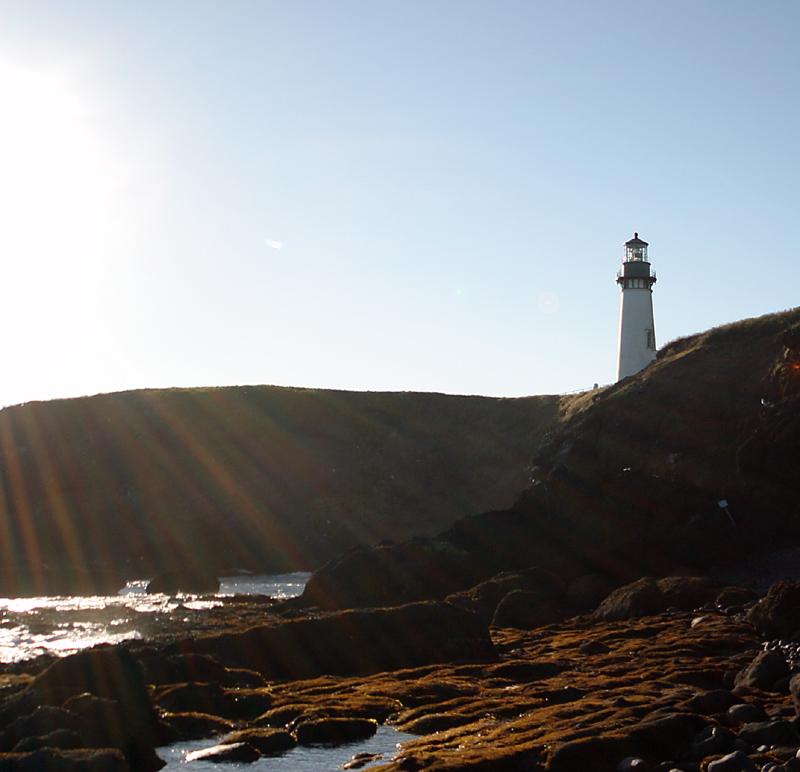 Oregon Coast Lighthouse from beach with suns rays.jpg