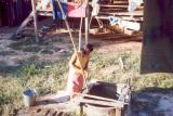 018 - Girl working at laundry, retrieving bucket from the well