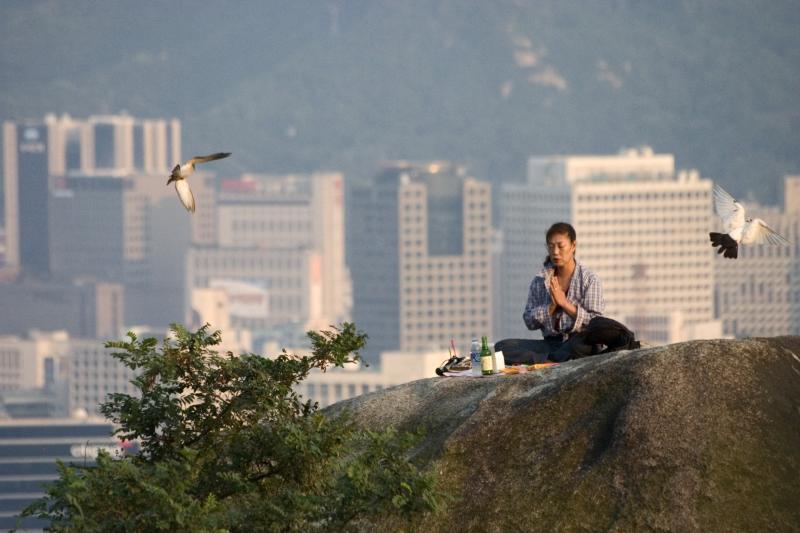 woman praying on Ingwansan Shamanist Hillside (James Hendrik)