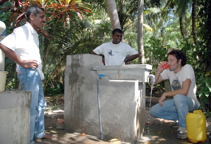 FCA staff demonstrate drinking disinfected water from the UV Tube