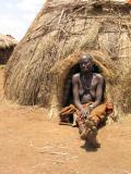 Mursi woman in front of hut