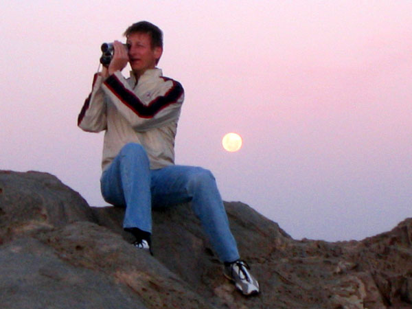 Ralph filming sunset on the cliffs at Lüderitz with the moon rising