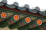 Detail of colorfully painted beams and ornate roof tiles, Gyeongbokgung