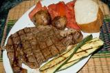 charcoal grilled ribeye steak, grilled zucchini, pan roasted potatoes, tomato salad