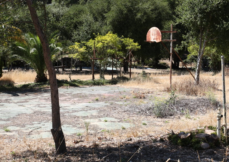 Basketball court and punching bags (minus bags) located next to swimming pools