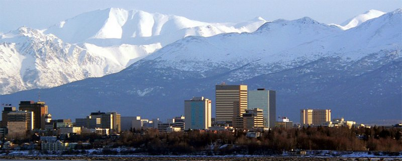 ANCHORAGE BY DAY WITH THE MIGHTY ALASKA COASTAL RANGE IN THE BACKGROUND