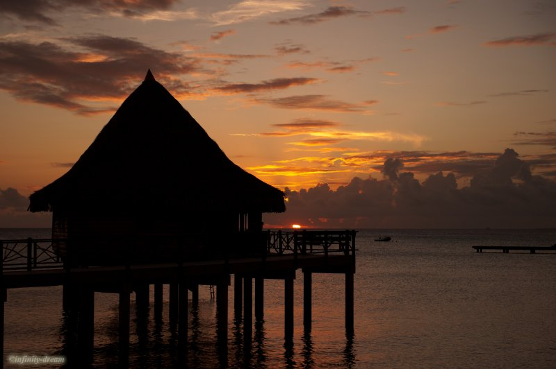 The sun setting behind the bungalow