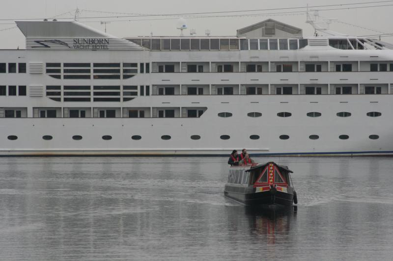 NB Earnest turns into the Pontoon dock with floating hotel in the background