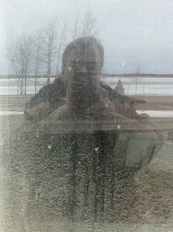 Paul reflected in (his own) dirty office window, the Moose River in background 2011 April 26