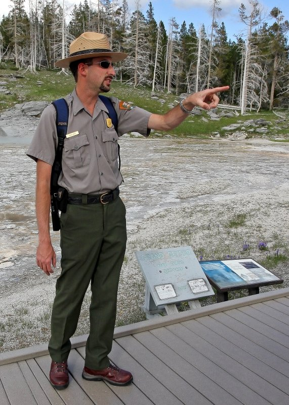 A Yellowstone National Park Ranger provides information in front of Grand Geyser