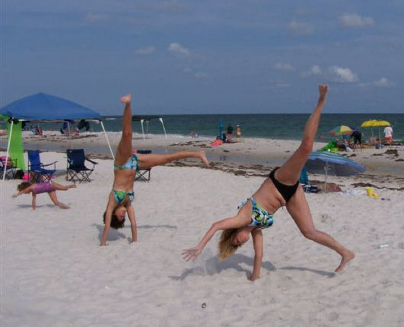 Hand stands in the sand. Ft - Bk daughter Amy,friend Kira and grand daughter Taylor. June 06