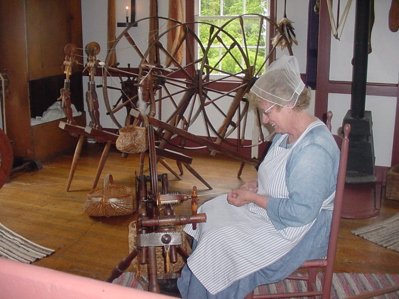 Notice the variety of spinning wheels, as a re-enactor spins thread.
