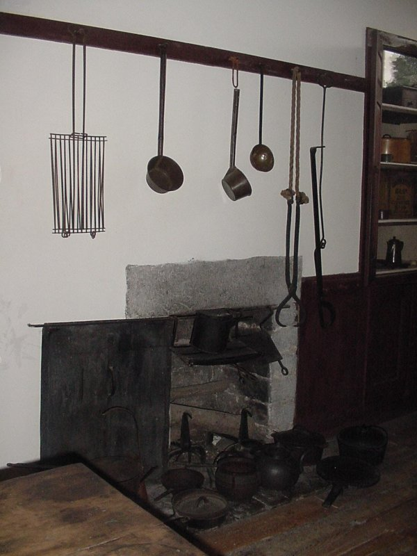 Kitchen utensils hanging above the open hearth used for cooking.
