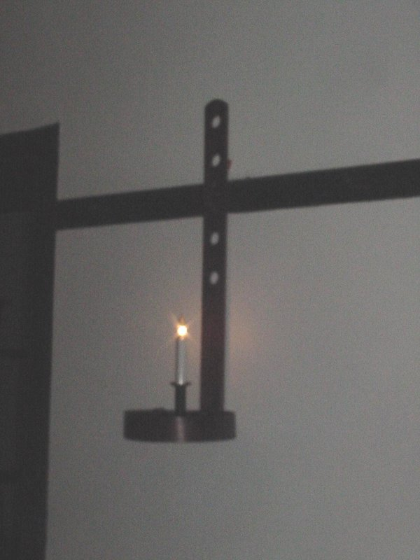 Homes were lit by candles in holders on the walls.  They could be removed & carried, if necessary.