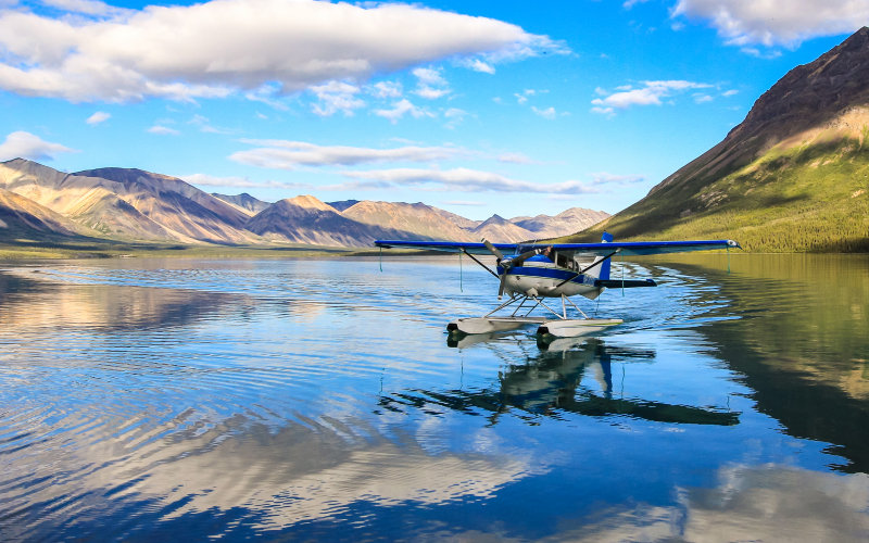 A pontoon plane taxies to the beach at Twin Lakes in Lake Clark National Park