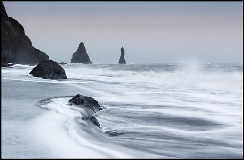 Stormwaves from south-east at Reynisdrangar near Vik with sand drift  over the ocean