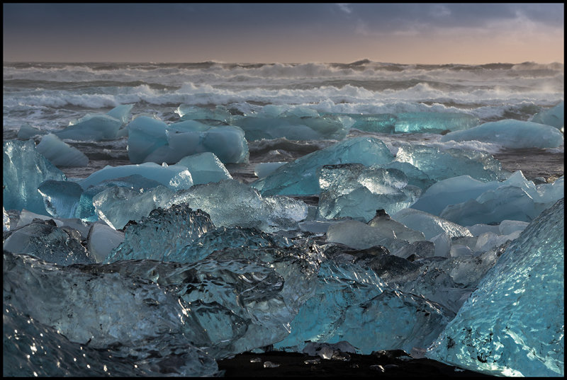 Ice from The huge glacier scattered on a lava beach near Jökulsarlon