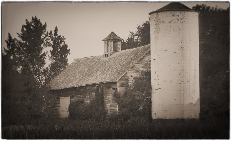 An Old Barn With a Concrete Silo