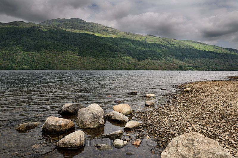 Rocky shore of Loch Lommond freshwater lake dividing lowlands from Scottish Highlands and Ben Lamond mountain Scotland UK