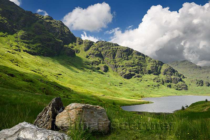 Beinn an Lochain and Binnein an Fhidhleir mountains of the Arrochar Alps in sun with Loch Restil at Rest and Be Thankful turnout