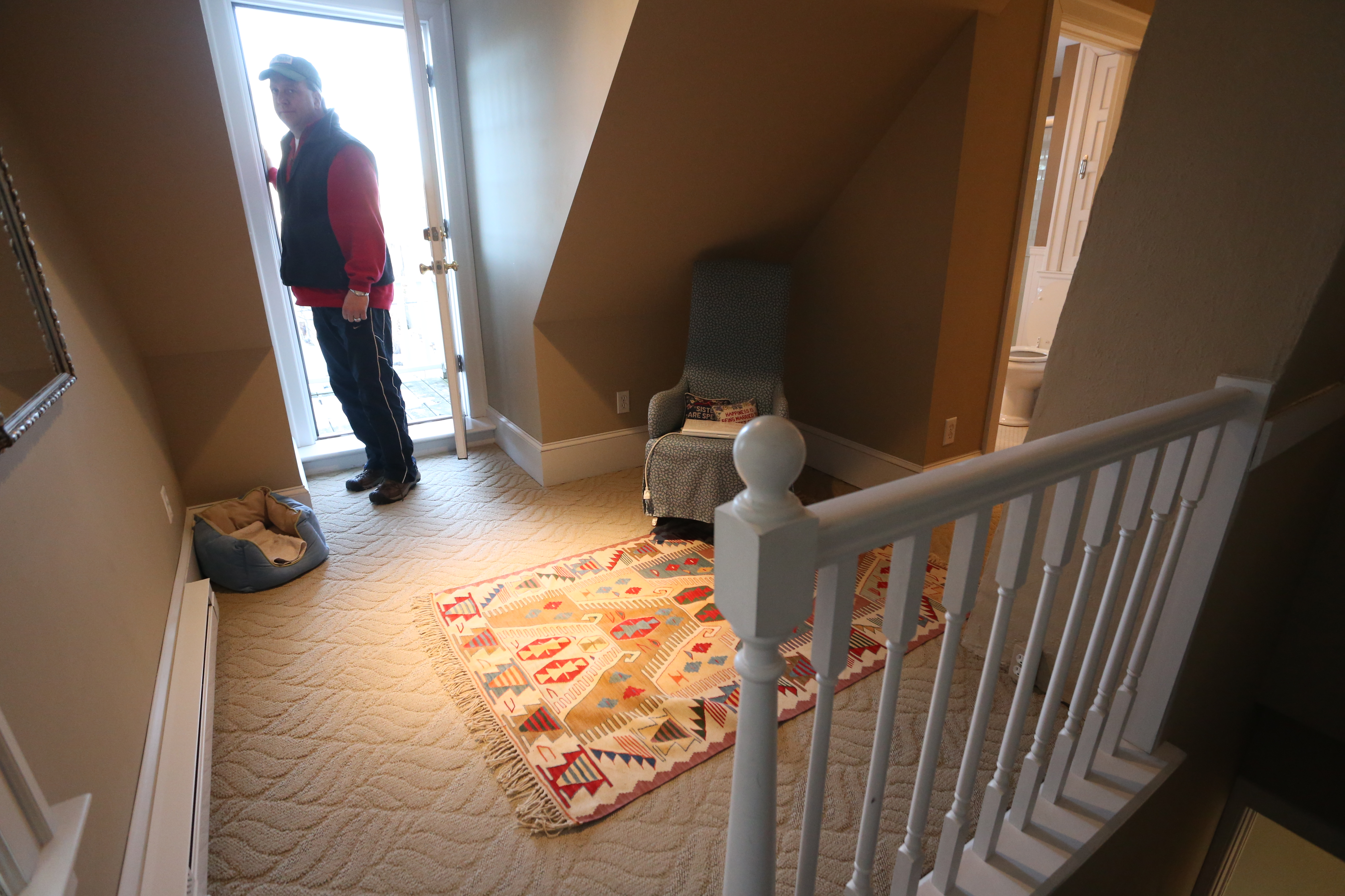 third floor master suite top of stairs facing small balcony