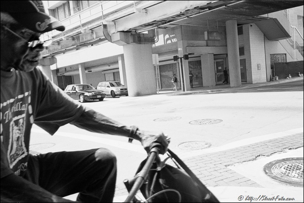 Man riding a bike in downtown Miami, Florida, USA, 2011. Street Photography of Miami, San Francisco and Key West by Emir Shabashvili, see http://street-foto.com, http://miamistreetphoto.com, http://miamistreetphotography.com or http://miamistreetphotographer.com